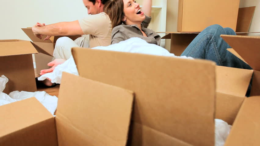 Young couple relaxing & laughing after unpacking cartons from house move