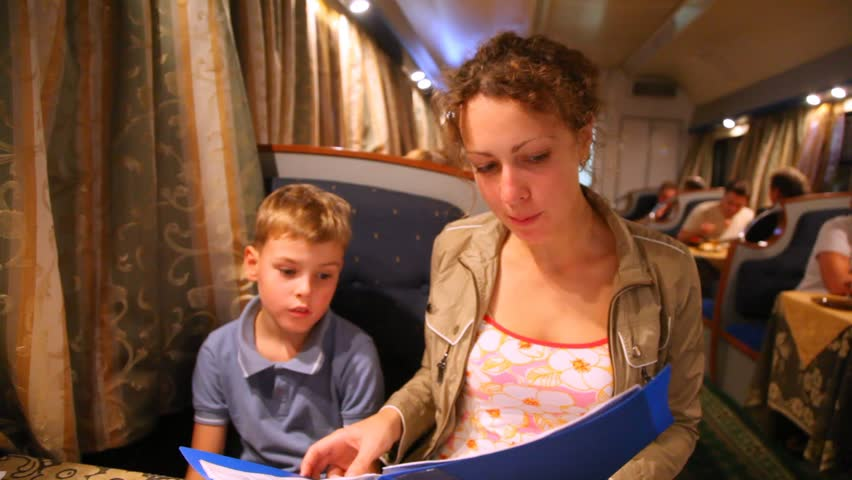 Mum and little son choose something in the menu in train