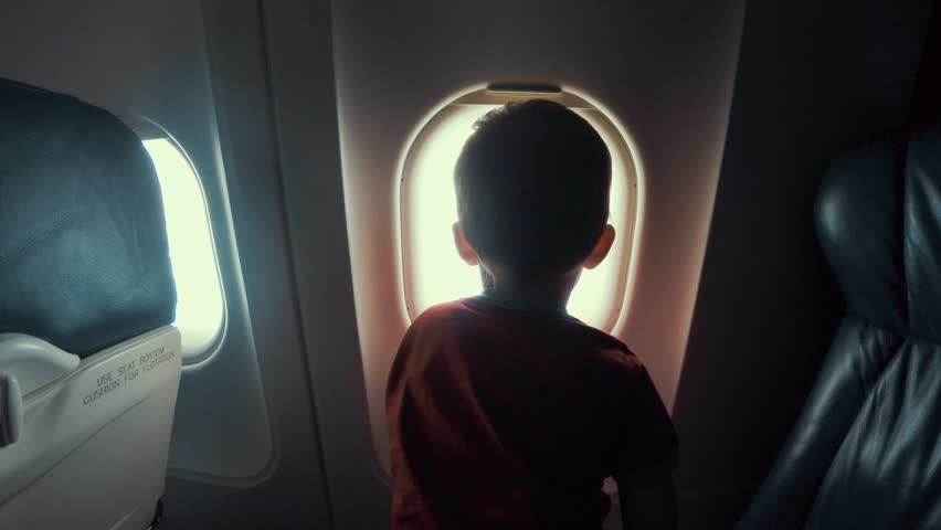 A young boy sitting on the seat looking out an airplane window while flying
