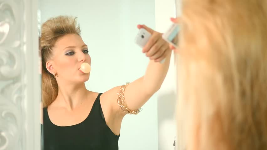Beauty punk style girl chewing gum in front of mirror and doing selfie photo. Stylish young lady with bouffant hairstyle smiling and hamming on smart phone camera. Adolescence. HD Video 1920x1080p