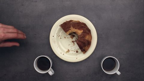 Cake and three cups of coffee on kitchen table, top view time lapse eating combined with stop motion animation.