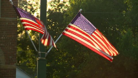 American Flags at the end of the day. They are glowing with the sun behind them. They are displaying local patriotism, affixed to an old brick building in a historic small town in the Midwest.