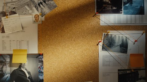 Detective puts two pieces of paper on evidence pin board with clues and suspects.