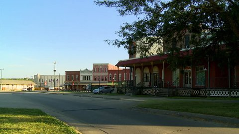 A great establishing shot of the quiet town of Fort Scott, Kansas on a summer evening. A few cars line the business district of this historic city. The buildings are ornate Victorian era structures.