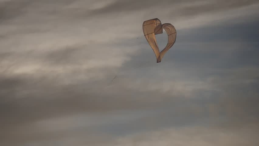 People Fly Heart-Shaped Kite Sky on Background Silhouettes Are Walking Along Seaside, Sea, Yellow Sunset, Horizon , Pier, boat at the sea, Tilt up, Tilt down, International Kite Festival, Outdoors,