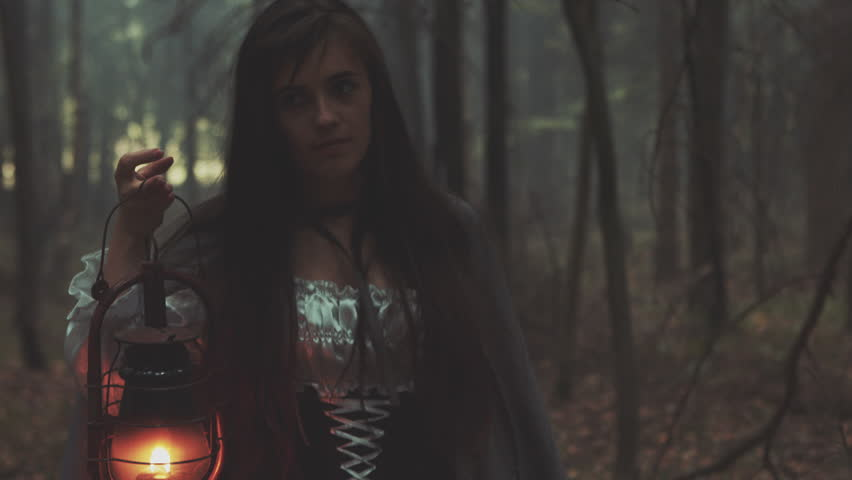 Young girl with a lantern wandering old forest. Gothic scene from the movie.