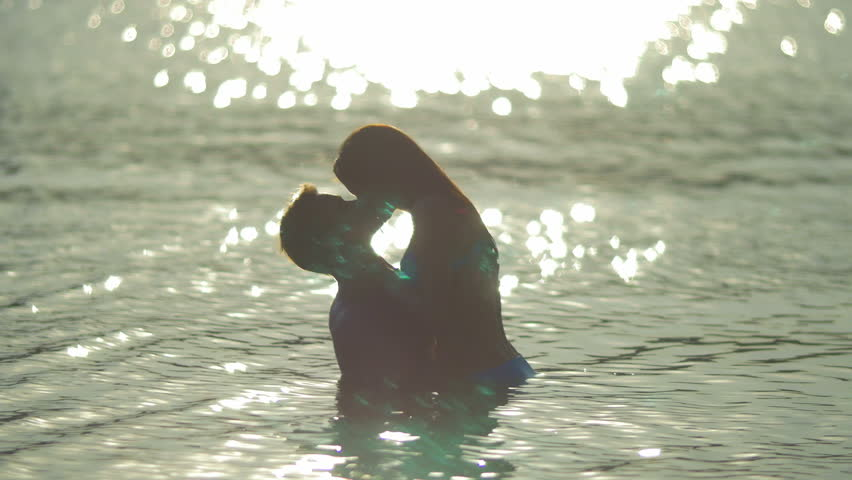 8 in 1 video! The couple (pair) walk on the beach and hug and kiss in the water with bright reflection surface. Real time and slow motion capture.