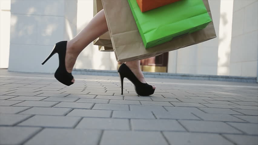 Sale, consumerism: Confident lady at heels with shopping bags walking after in a city. Slow motion | Shutterstock HD Video #11734121