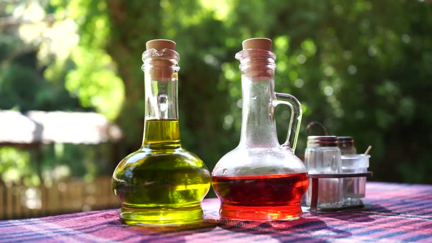 Olive oil and vinegar in glass bottles on a table outside on an open terrace in Blue Eye in Albania