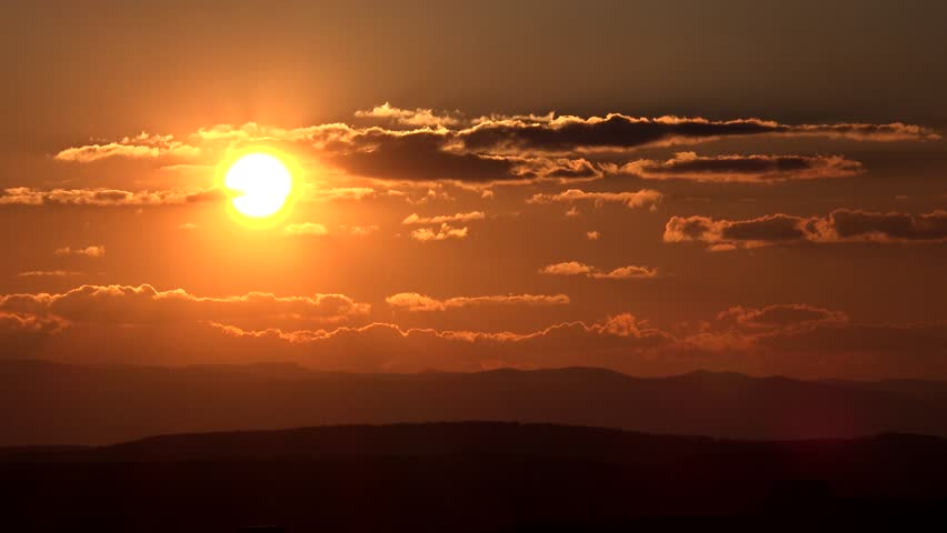 4K Timelapse of sun silhouette at sunrise or sunset, peaceful ray light among cloud, misty skyscape by day #11778191