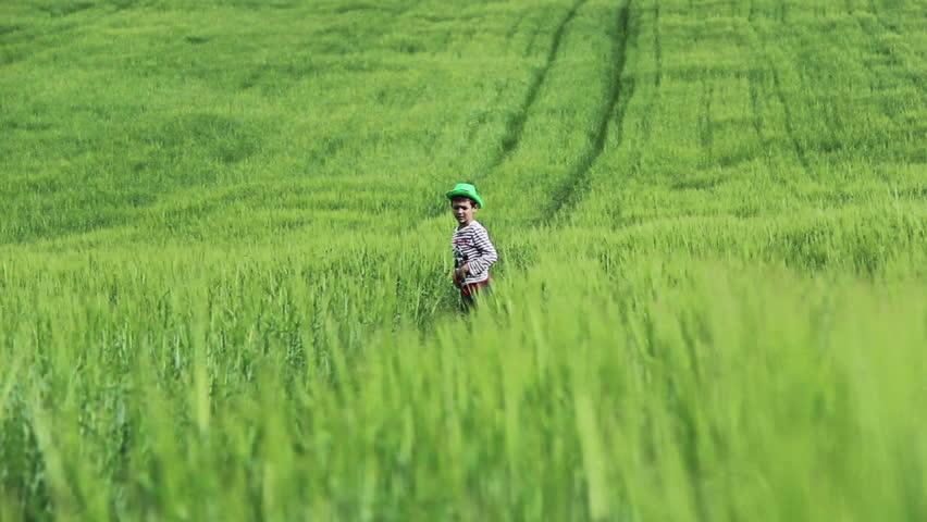 tall green grass field. Boy In Green Hat Running On The Field Among Grass, Front View, Tall Spends Time Farm, Village, Jumps Raises Grass