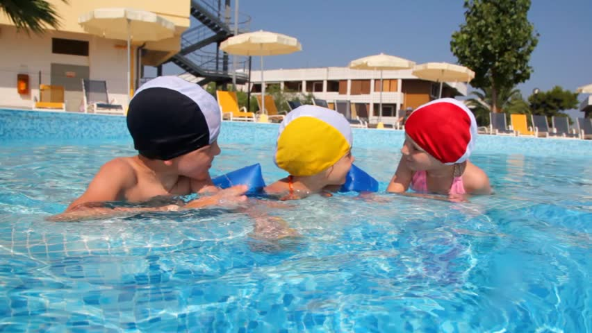 Boy and two girls in swimming caps are talking in the pool