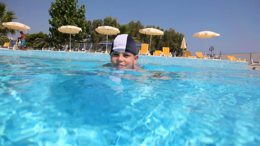 Boy in swimming cap in the pool water, the camera goes under water, and shows how he floats