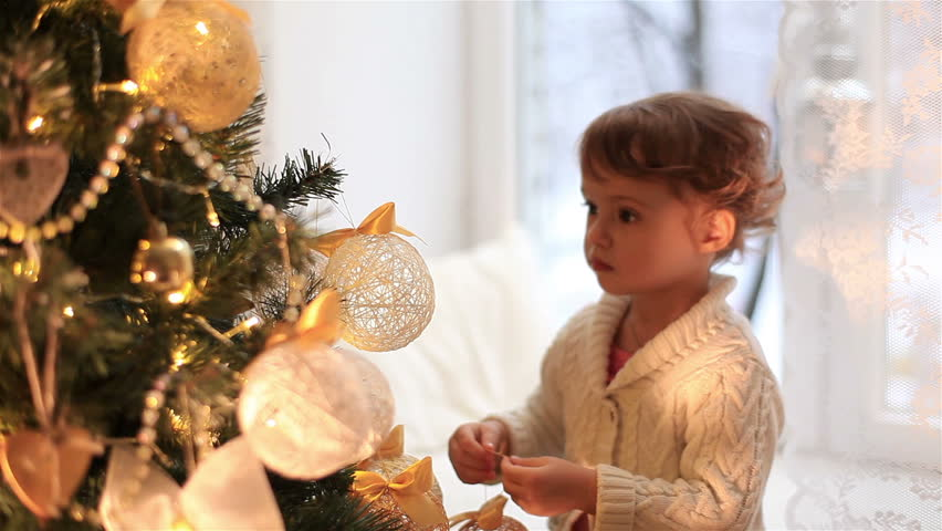 Cute little girl decorates the Christmas tree.