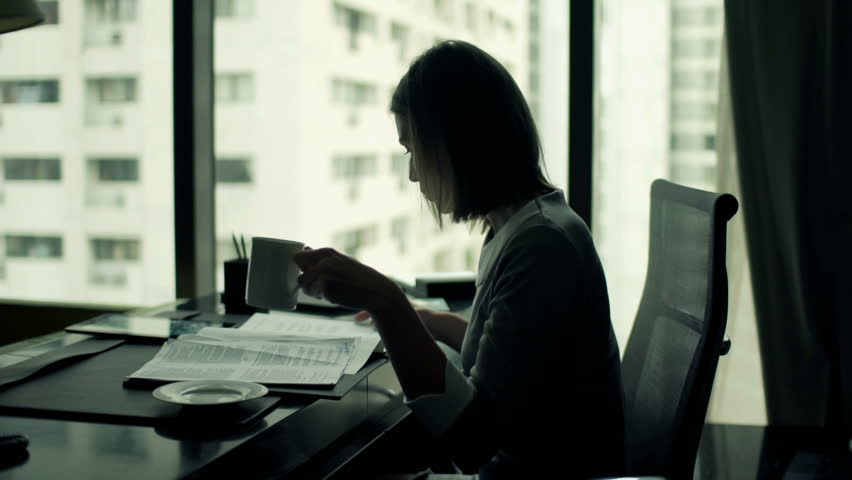 Young businesswoman reading documents and drinking coffee while sitting by desk in office  | Shutterstock HD Video #11826941