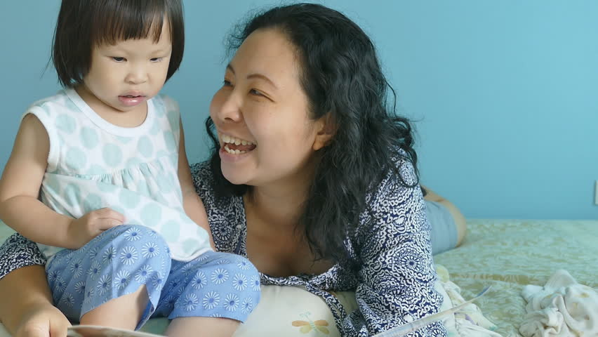 Asian mother telling a story to her baby in the bedroom  | Shutterstock HD Video #11843207