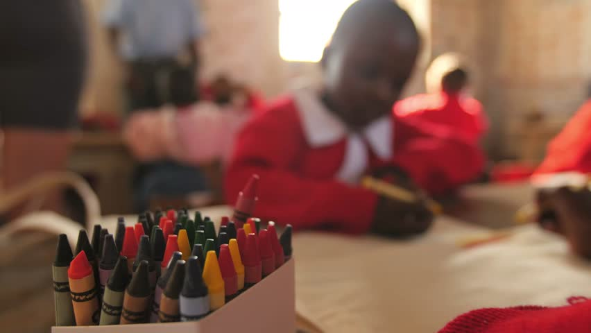 Children choose crayons and color pictures at a school in Kenya.