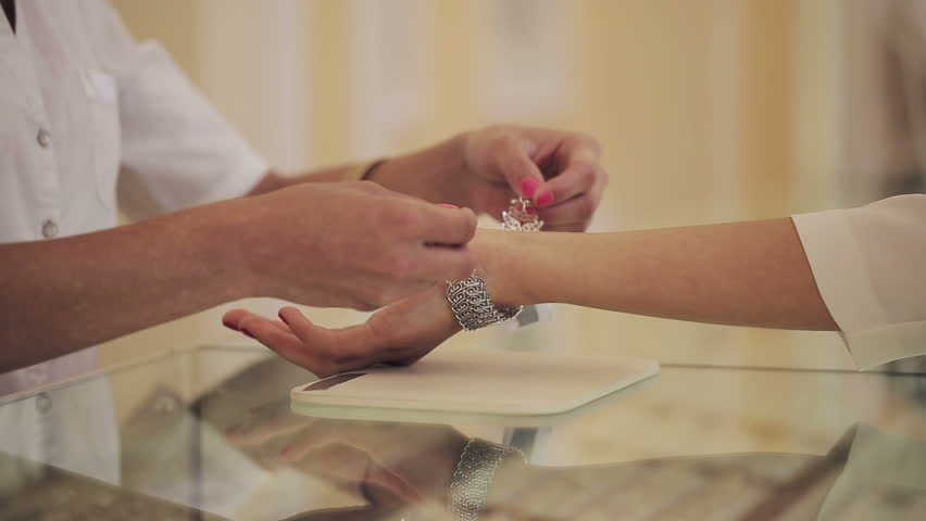 Jewelry store: Young woman tries on expensive bracelet. Close up