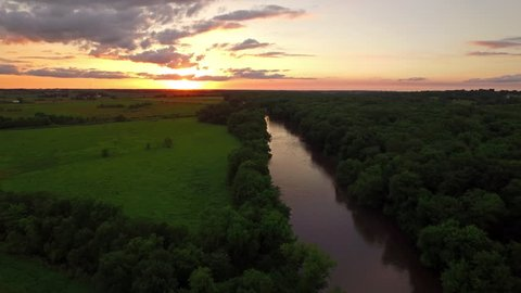 Aerial video of the countryside in Iowa. Farms at sunset. Freeway.