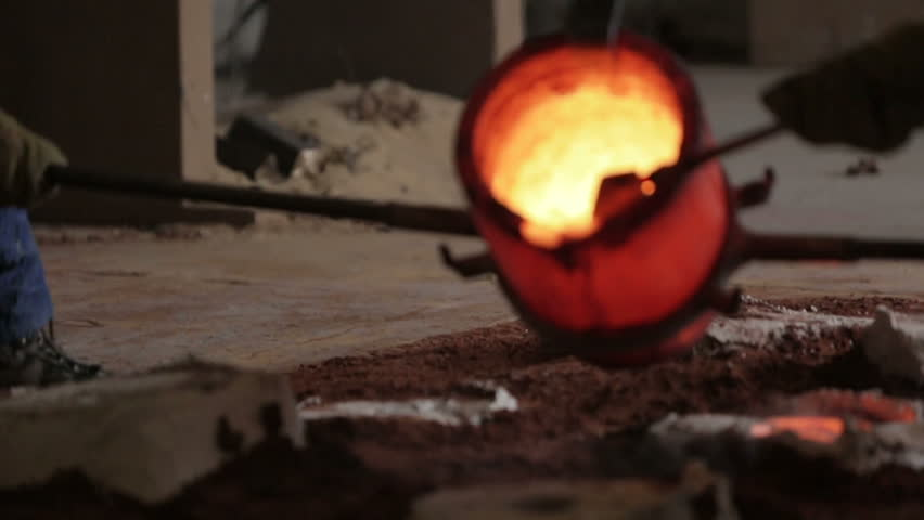 Workers in a bronze foundry pouring bronze into investments for a bronze statue