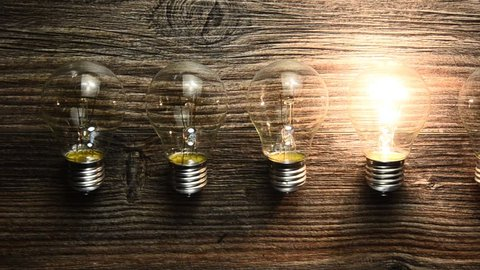glowing bulb on the brown wooden background. Many lamps and lights up only one. concept ideas