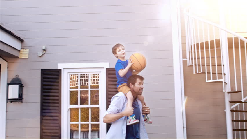 4k wide shot of father and son dunking the basketball in hoop on home driveway with sunflare.