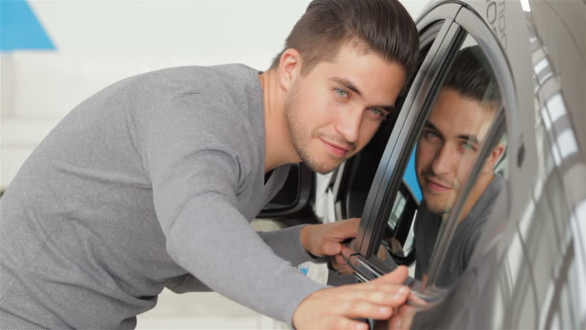 A man inspects his new car color. Auto business, car sale, technology and people concept - happy male with car dealer in auto show or salon. Young man with a salesman in a motor show.