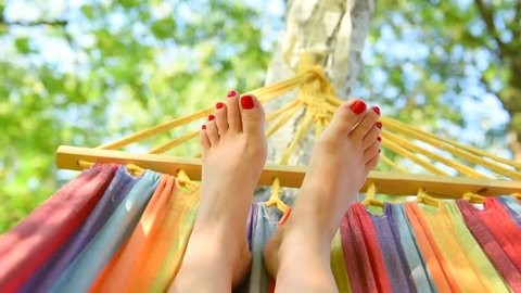 Young woman lying and resting on a Hammock barefoot and move her bare feet. Good mood concept. Relaxing outdoor. Summertime vacation. Video 240 fps. HD 1920x1080p