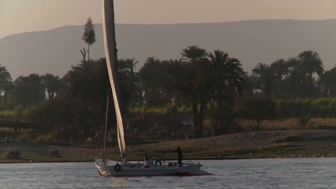 Egyptian Felucca foreground on Nile River with camel train background, Egypt.