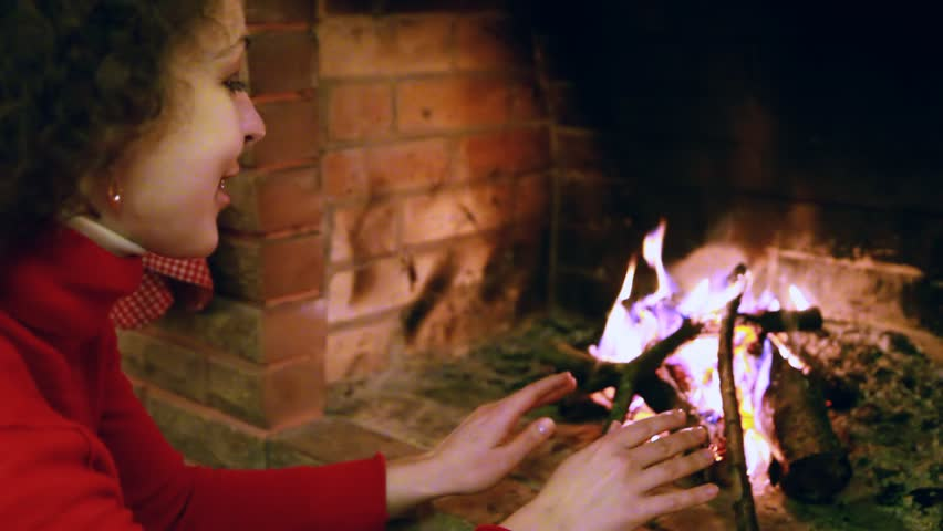 beautiful woman in red sweater sits by fire warming his hands
