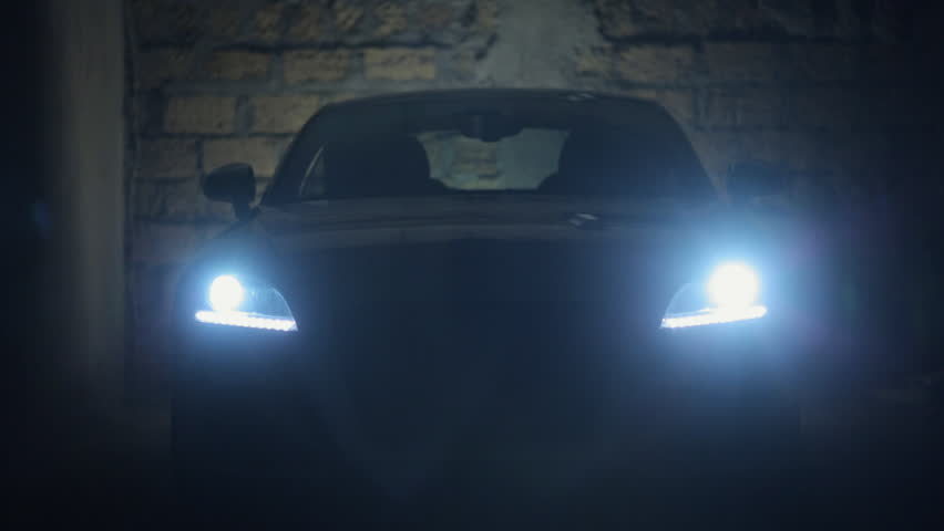 Turn on the headlights of car in a dark stone garage | Shutterstock HD Video #11950751