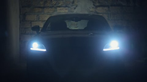 Turn on the headlights of car in a dark stone garage