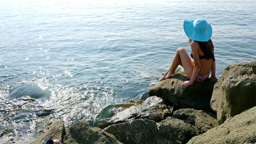 Young woman in swimming suit and blue hat sitting on rocks on the sea shore #11951021