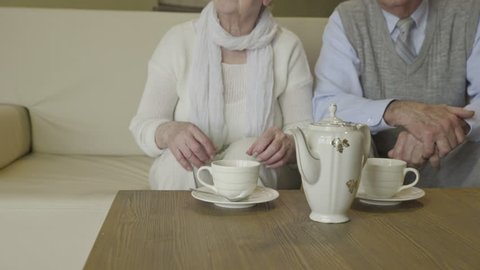 Elderly person pour tea in to cups 4K. Close up of grandparents sit on sofa and pour some tea in white tea cups.