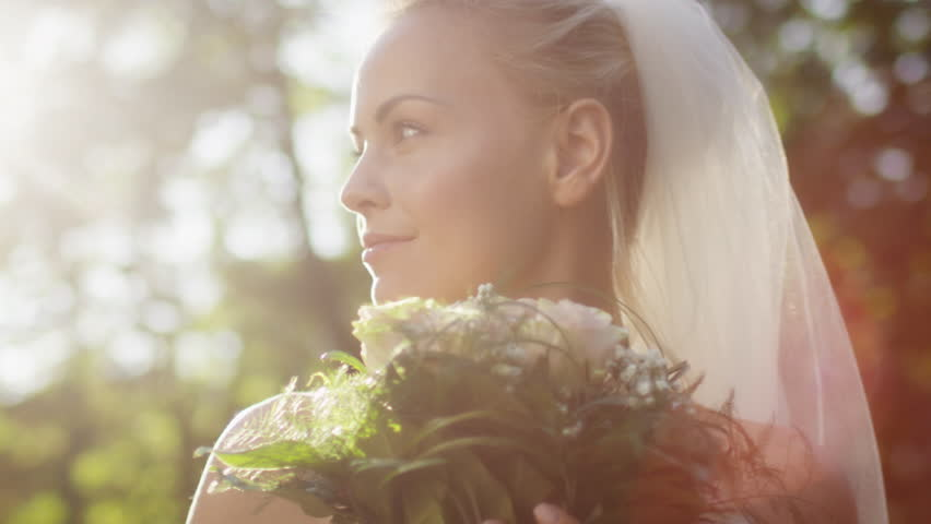 Portrait of a bride in wedding dress with flowers in a sunny park. Shot on RED Cinema Camera in 4K (UHD).