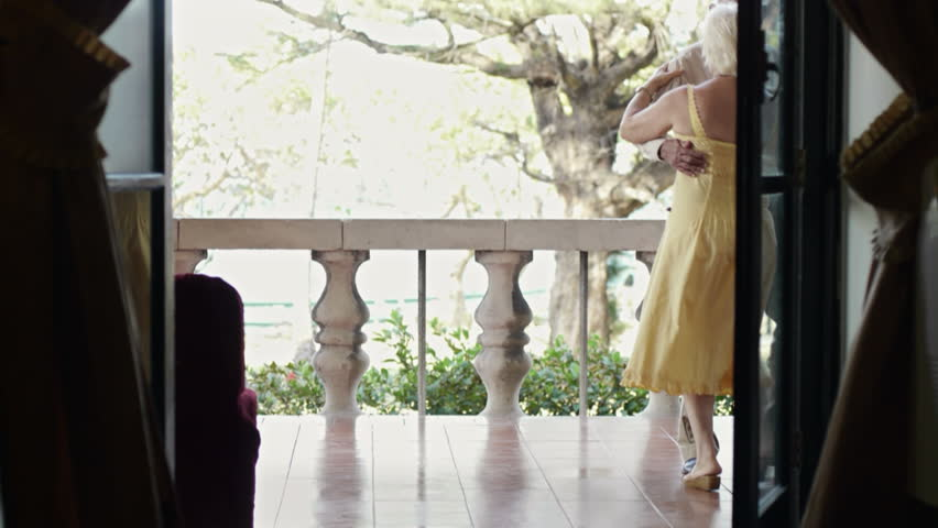 senior caucasian couple on vacation, dancing on terrace in hotel