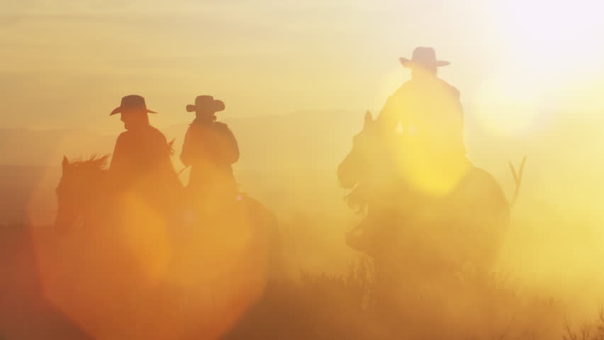 Cowboys riding into the golden sunset at dusk with mountain range background, slow motion with strong sun lens flares.