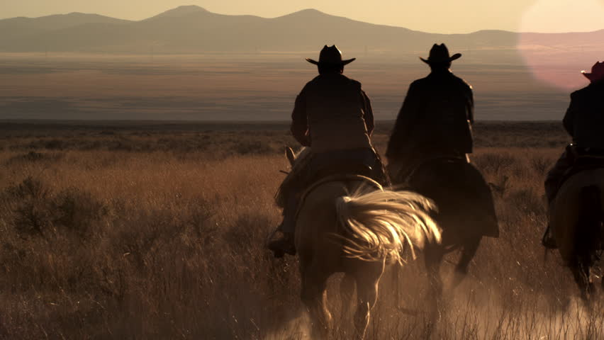 Dusk shot of four cowboys riding off into the sunset towards mountains in the background. They leave a trail of dust behind them.