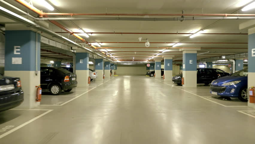 4K Pov drive through underground parking garage,real time.4K Real time vehicle dashboard driving pov through a huge underground parking garage of a big mall/shopping centre.Parking at a free spot.