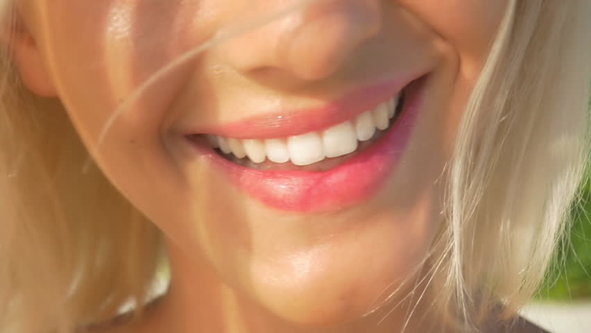 SLOW MOTION CLOSE UP: Beautiful blonde girl smiling, showing her perfect white teeth