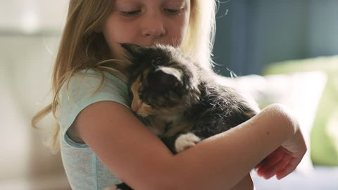 A kitten licks a little girl's face while she's holding it