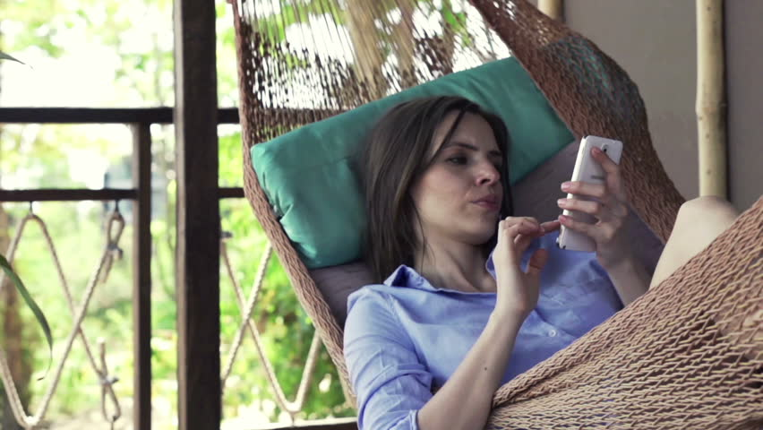 Young woman with smartphone lying on hammock   | Shutterstock HD Video #12010661