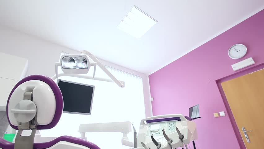 A Dental Clinic Interior Design Purple Chair With Tools And Lamp Over Wall