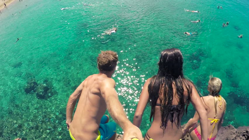POV GOPRO HD Slow Motion Group of friends jumping from cliff into the ocean in Hawaii. Summer fun lifestyle.