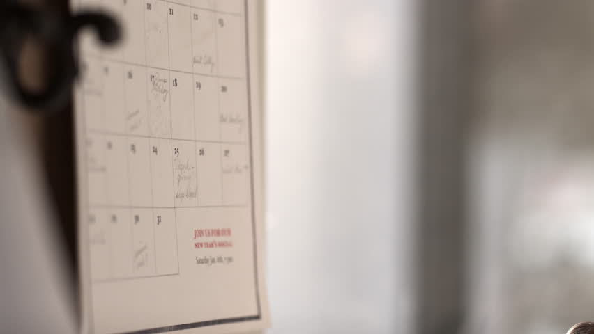 Close up of hand writing on calendar