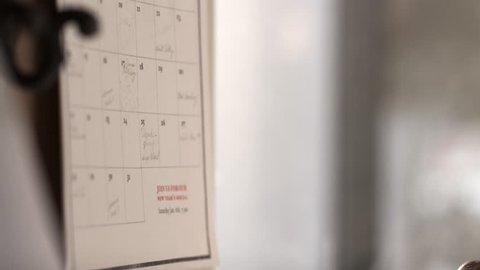 Close up of hand writing on calendar