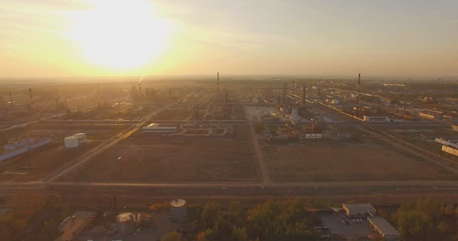 Beautiful industrial plant with large pipes at sunset. Top view. Aerial. The smoke from the chimneys. Excellent video for movies and advertisements about the production, technology and business.
