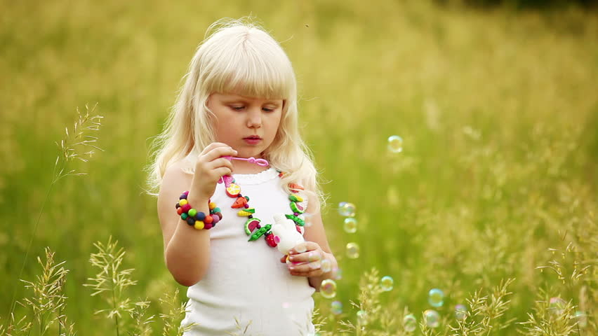 Child blowing bubbles. She laughs and look at camera.