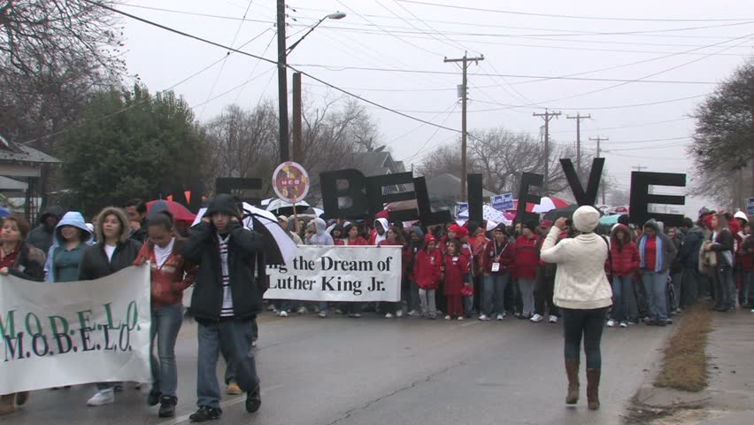Video of the largest Martin Luther King MLK March in the USA in San Antonio, Texas. Multi ethnic support of equal rights. Misty rainy day in January. We Believe sign.