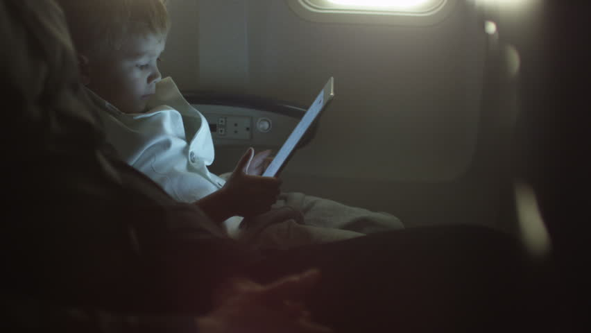 Young Boy Is Playing With Tablet On An Airplane Next To A Window. Shot On